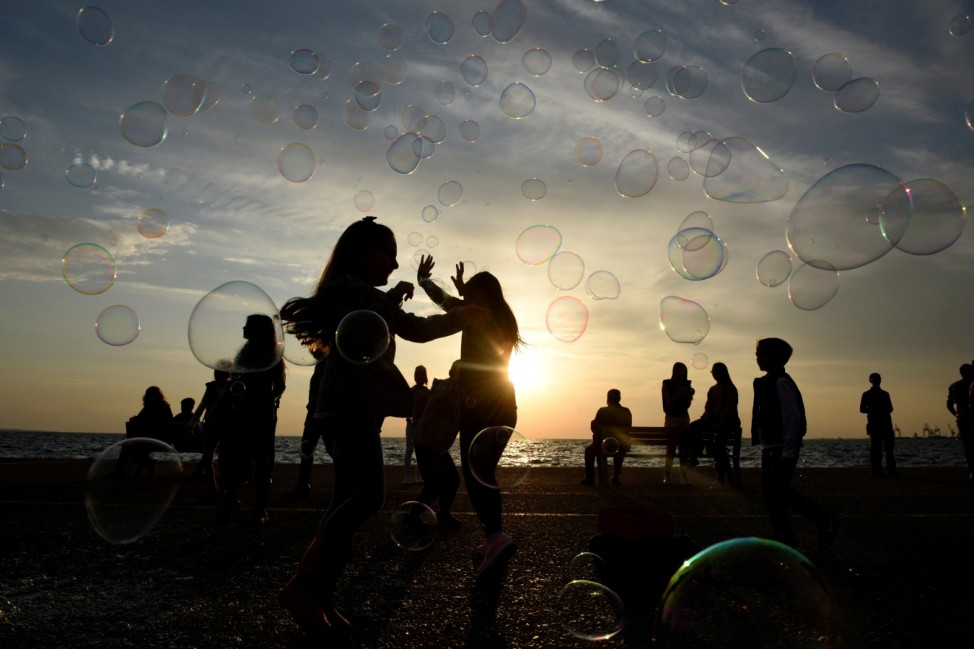 Children play with soap bubbles at the seaside promenade of Thessaloniki