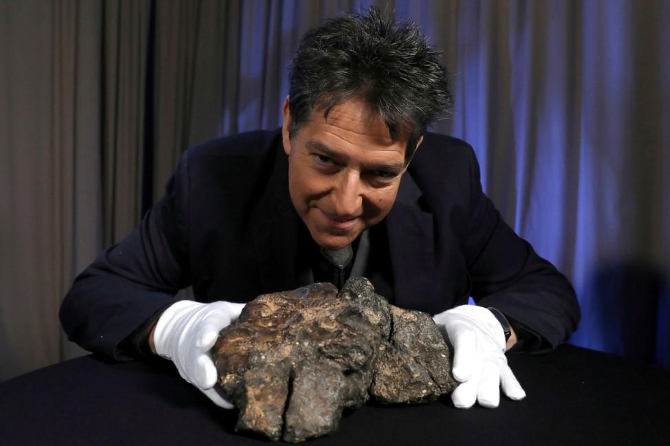 Geoff Notkin, CEO of Aerolite Meteorites, Inc. poses with a Lunar Meteorite ahead of auction in New York