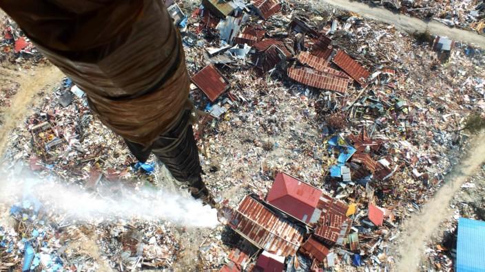Entwicklungspolitik: Die Weltbank unterstützt oft Länder, die von Katastrophen betroffen wurden, wie hier etwa Indonesien. Im Bild: Ein Hubschrauber verteilt im Oktober 2018 nach einem Erdbeben Desinfektionsmittel in der Gegend von Palu, um die Ausbreitung von Seuchen zu verhindern.