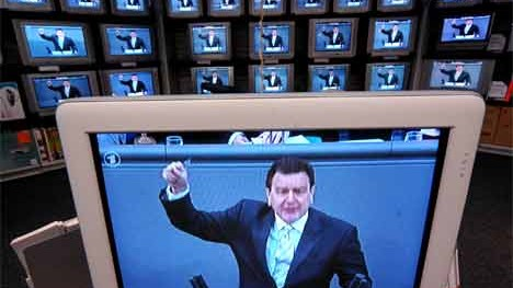 Gerhard Schröder, zu sehen bei einer Bundestagsrede auf zahlreichen TV-Schirmen