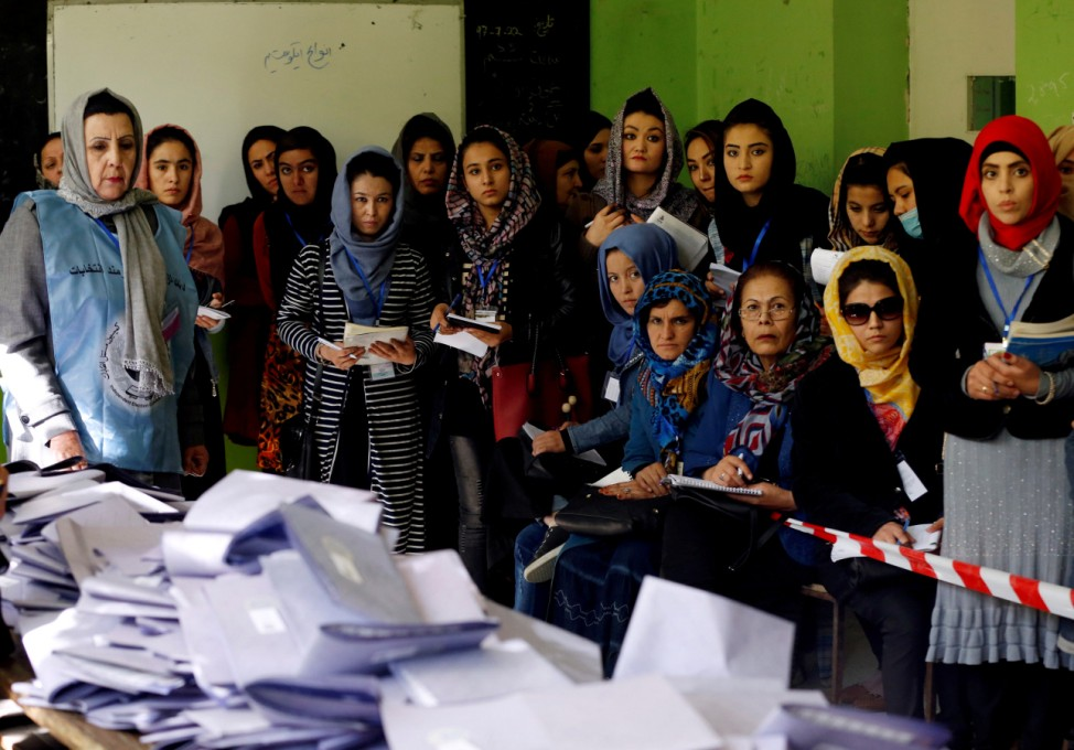 Election observers watch the counting of ballots during parliamentary elections at a polling station in Kabul