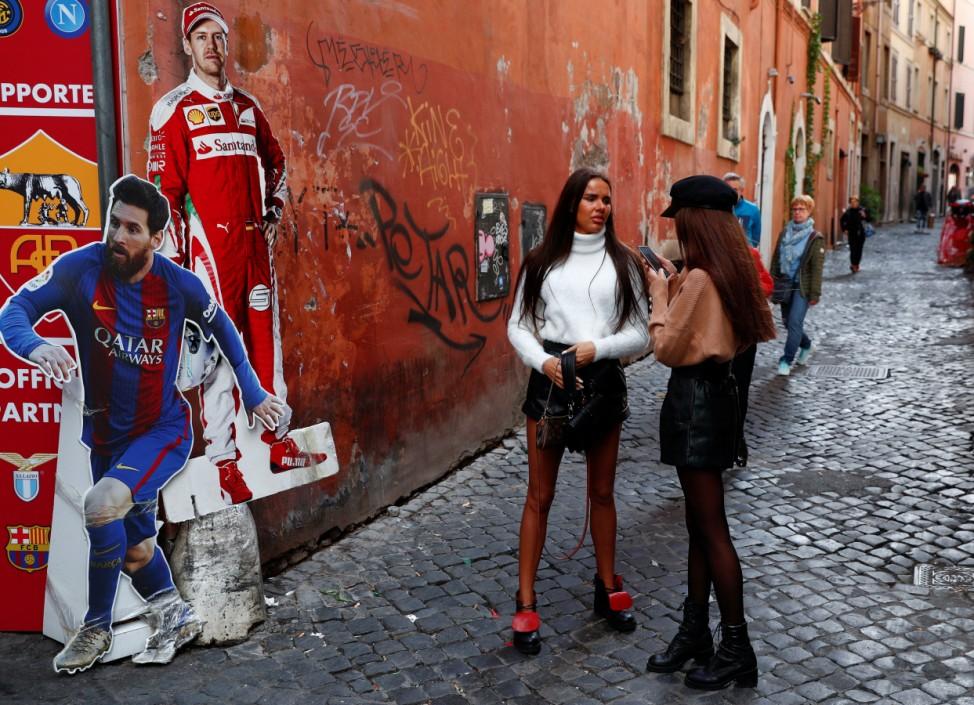 Women talk next to life-size cardboard cutouts of soccer star Lionel Messi and Ferrari driver Sebastian Vettel in Rome