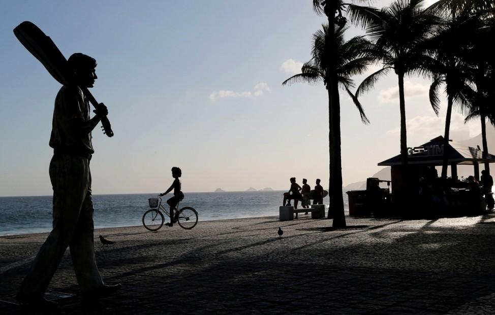 A woman rides her bicycle near the statue of Brazilian musician Tom Jobim at Arpoador beach in Rio de Janeiro