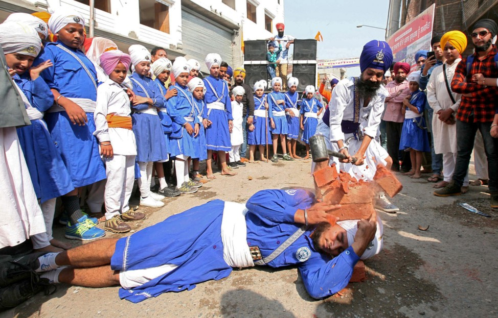 A Nihang or Sikh warrior uses a hammer to break bricks on the head of another Sikh as they perform Gatkha in Amritsar