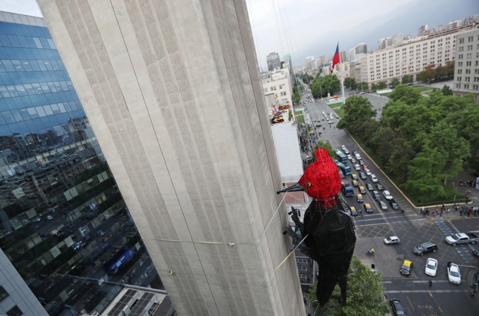 A model of a woodpecker is placed on a communication tower as part of the 'Hecho en Casa' (Made at Home) art installations in Santiago