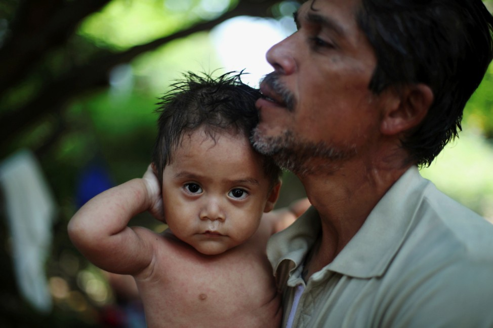 Eddie, from Guatemela, is held by his father Julio Garcia Marquez while resting amid others from Central America en route to the United States, in Tapanatepec, Mexico,