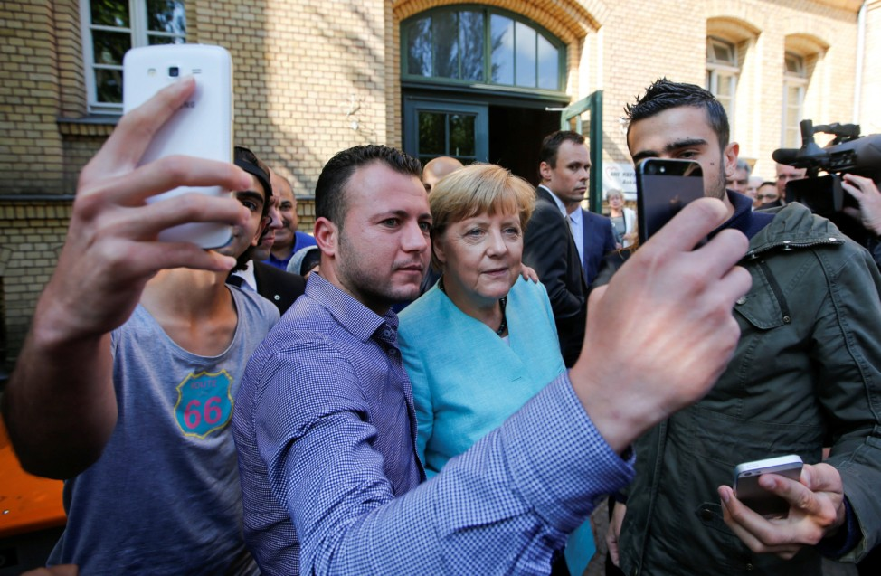 FILE PHOTO: Migrants from Syria and Iraq take selfies with German Chancellor Merkel outside a refugee camp in Berlin