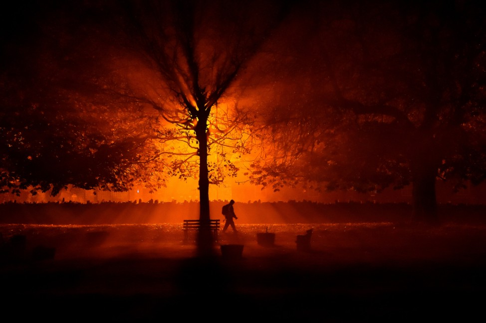 A man uses a torch to walk through a park during cold fog at night in Athboy