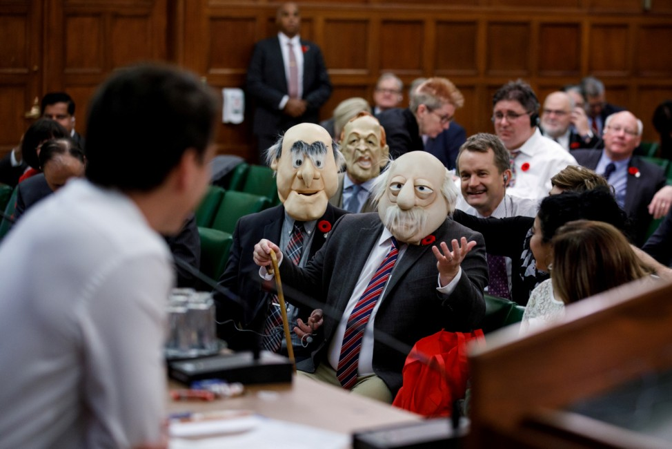Canada's Prime Minister Justin Trudeau is met with people wearing the face masks of Muppets characters Waldorf and Statler in Ottawa