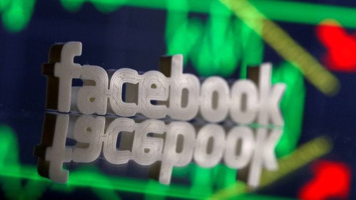 FILE PHOTO: A 3D-printed Facebook logo is seen in front of displayed stock graph