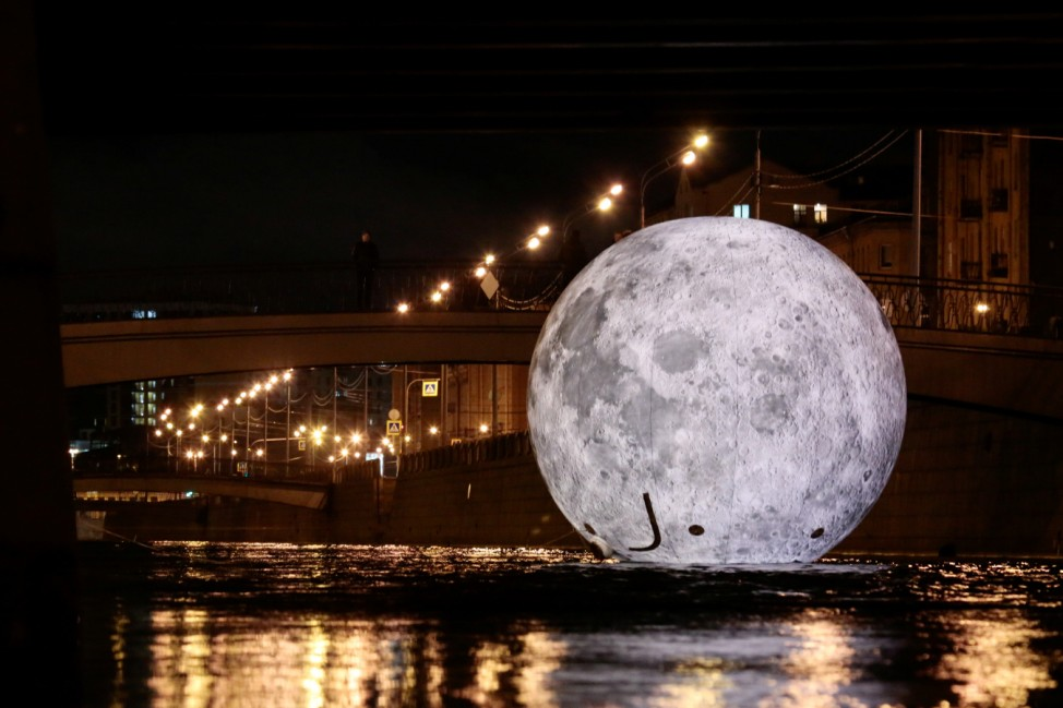 A giant ball decorated with images of the moon's surface, an installation for the 'Festival of Lights', is seen in the water of Obvodny channel in Saint Petersburg