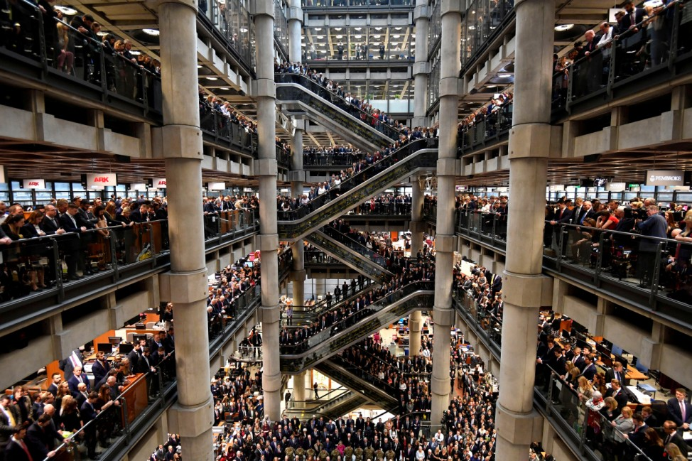 Workers stand during a Remembrance Service at the Lloyd's building in the City of London