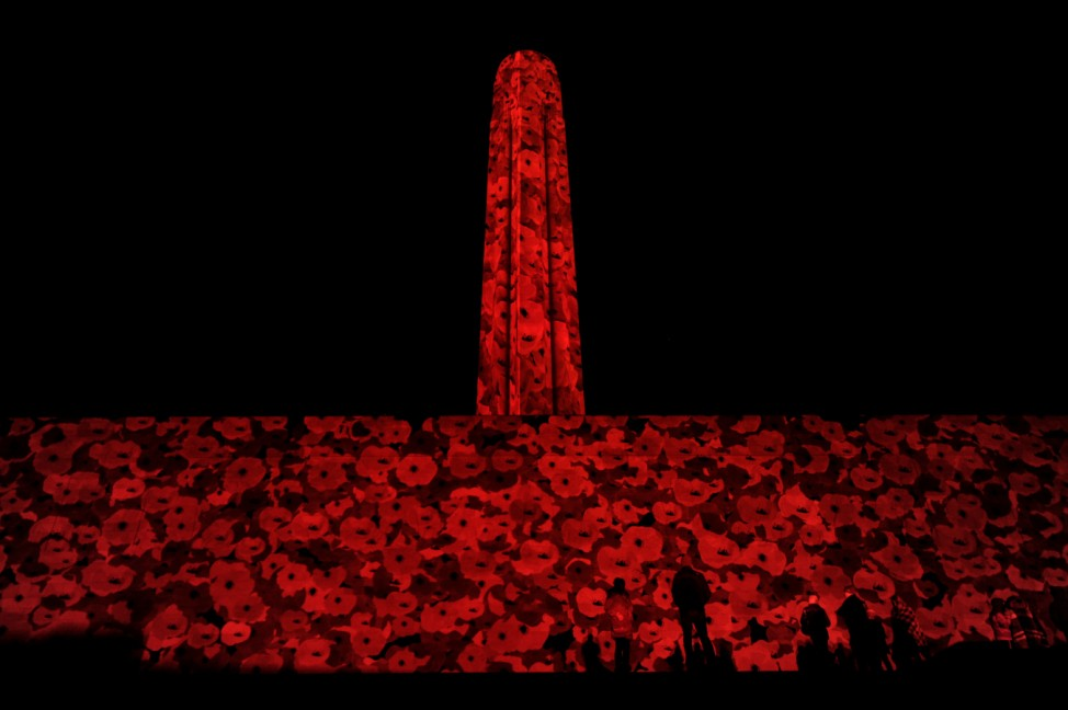 Visitors view the more than 5,000 poppies projected on the facade of the Liberty Memorial at the National WWI Museum and Memorial in Kansas City