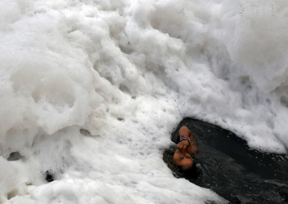 A Hindu woman takes a dip in the polluted waters of the river Yamuna during the Hindu religious festival of Chatth Puja in New Delhi