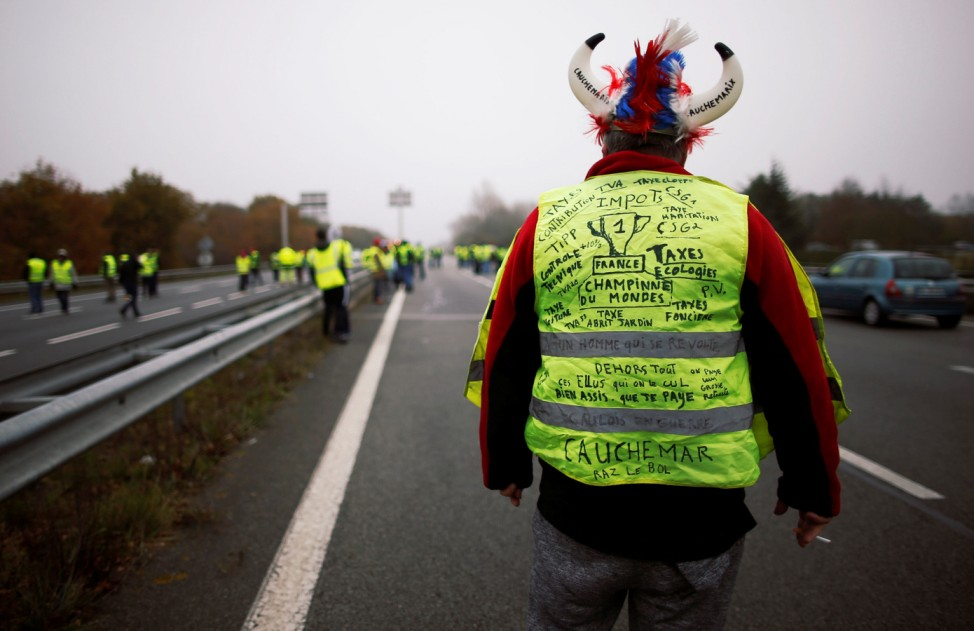 A protester wearing a yellow vest, a symbol of a French drivers' protest against higher fuel prices, blocks a road in Donges