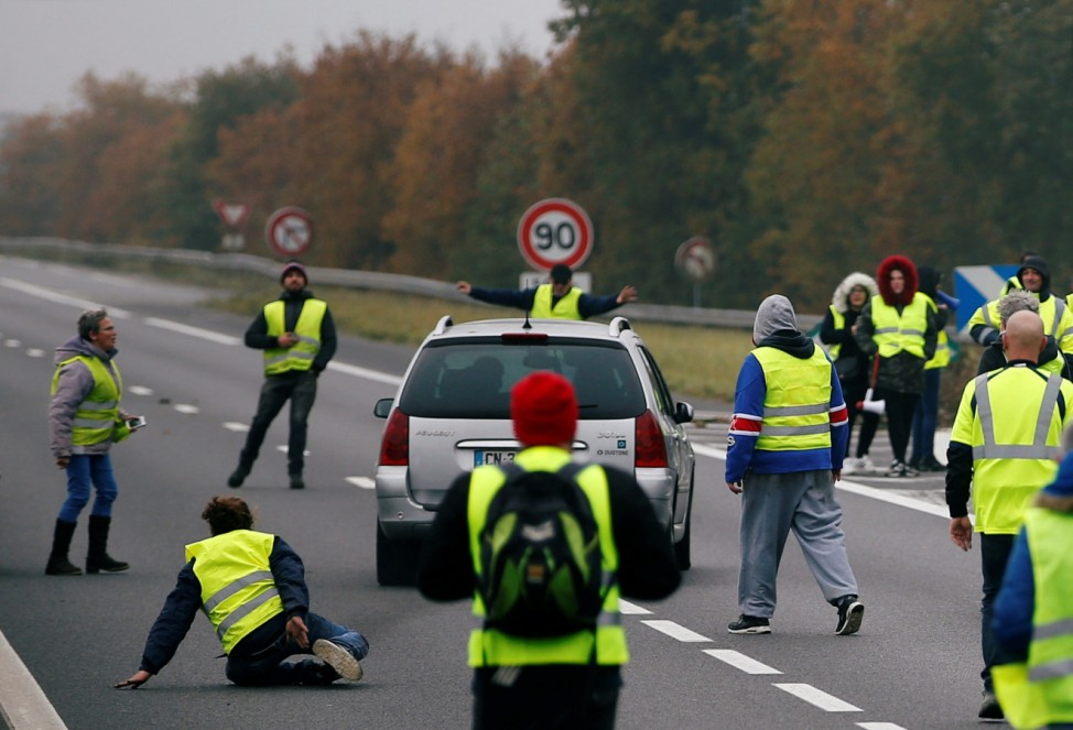 A car forces a dam as protesters wearing yellow vests, a symbol of a French drivers' protest against higher fuel prices, block a road in Donges