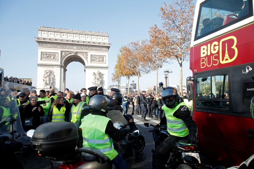 People wearing yellow vests, a symbol of a French drivers' protest against higher fuel prices, gather near the Arc de Triomphe in Paris