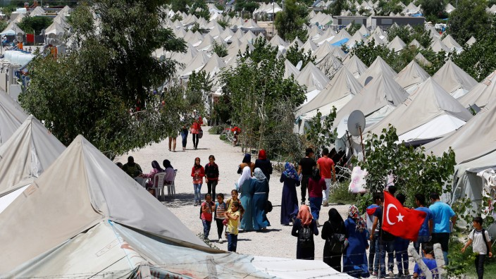 Syrian refugees stroll at a refugee camp in Osmaniye