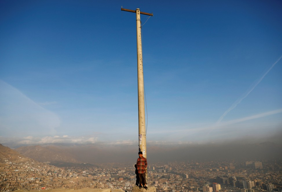 An Afghan boy stands in the sun on a hilltop overlooking Kabul, Afghanistan