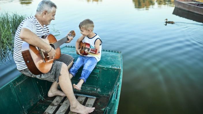 Grandfather teaching grandson playing guitar model released Symbolfoto PUBLICATIONxINxGERxSUIxAUTxH