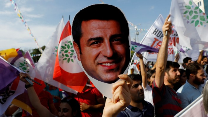 FILE PHOTO: A supporter of the pro-Kurdish HDP holds a mask of their jailed former leader and presidential candidate Demirtas during a rally in Ankara