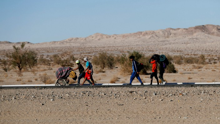 Migrants, part of a caravan of thousands traveling from Central America en route to the United States, make their way to Tijuana from Mexicali, in Mexicali