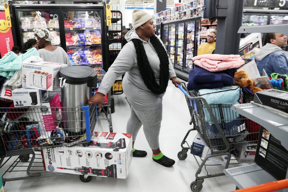 People wait in line to pay at a Walmart during a sales event on Thanksgiving day in Westbury, New York