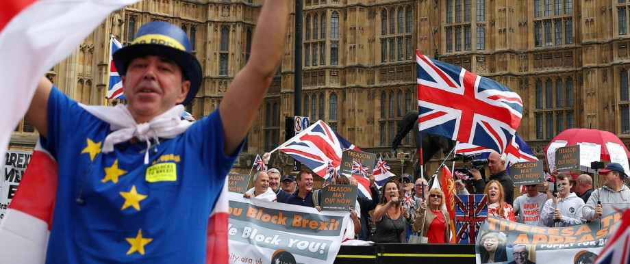 FILE PHOTO: Pro and anti Brexit protesters demonstrate on opposite sides of the road outside the Houses of Parliament in London