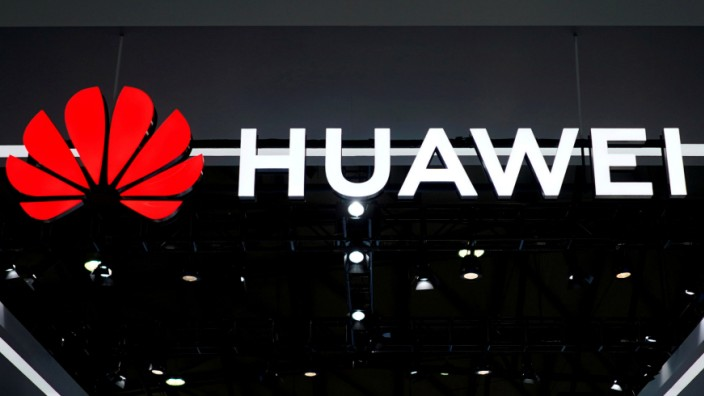 FILE PHOTO - People walk past a sign board of Huawei at CES (Consumer Electronics Show) Asia 2018 in Shanghai