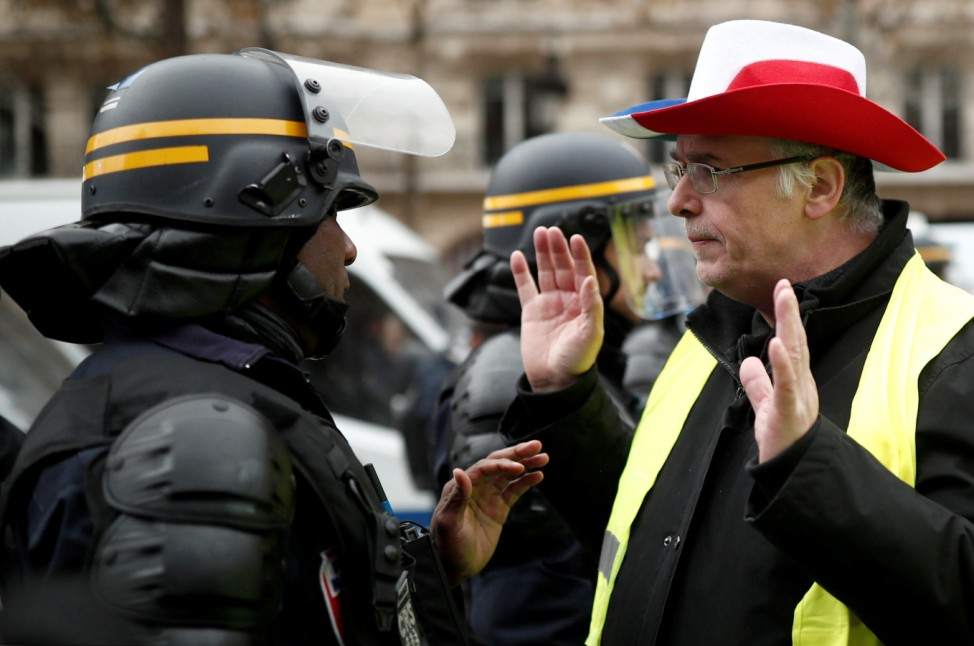 A protester wearing yellow vest, a symbol of a French drivers' protest against higher fuel prices, talks to the police officer on the Champs-Elysee in Paris