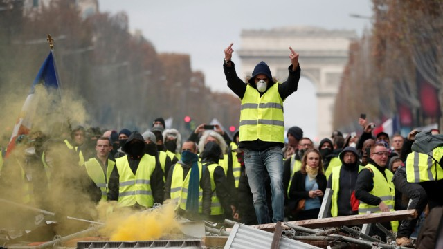 A protester wearing yellow vest, a symbol of a French drivers', protest against higher fuel prices, gestures during clashes on the Champs-Elysees in Paris