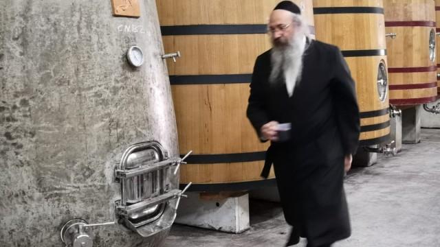 Ein Rabbiner kontrolliert Weinfässer in Israel.