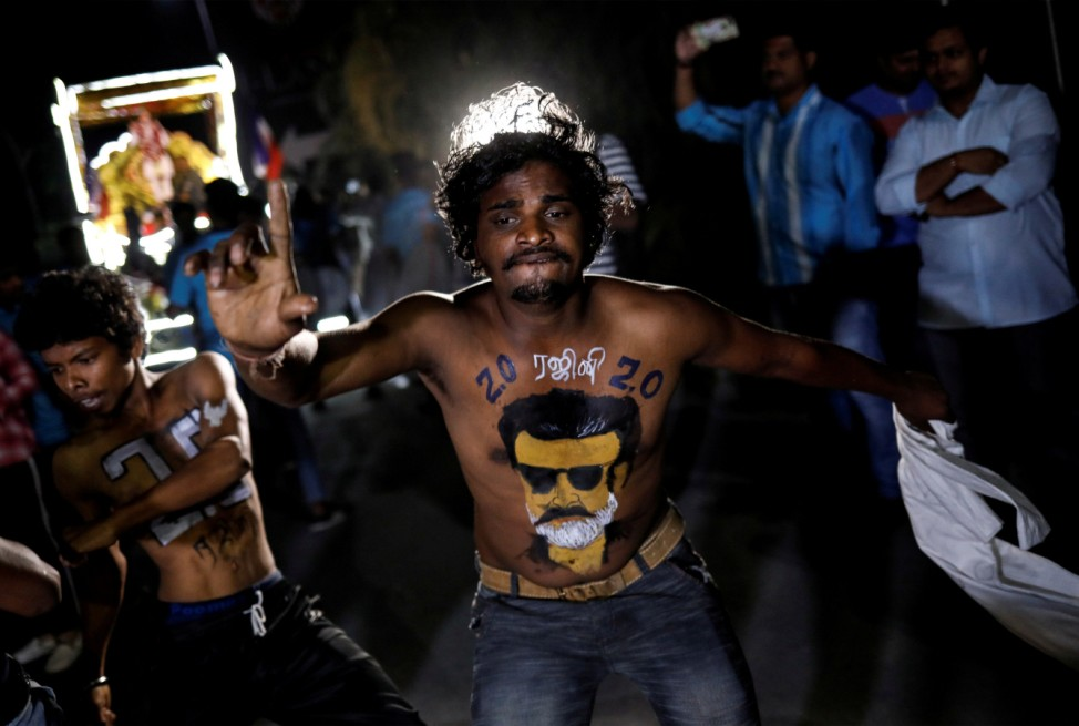 A fan with his body painted with image of Tamil film star Rajinikanth dances as he celebrates the release of his new movie '2.0' in Mumbai