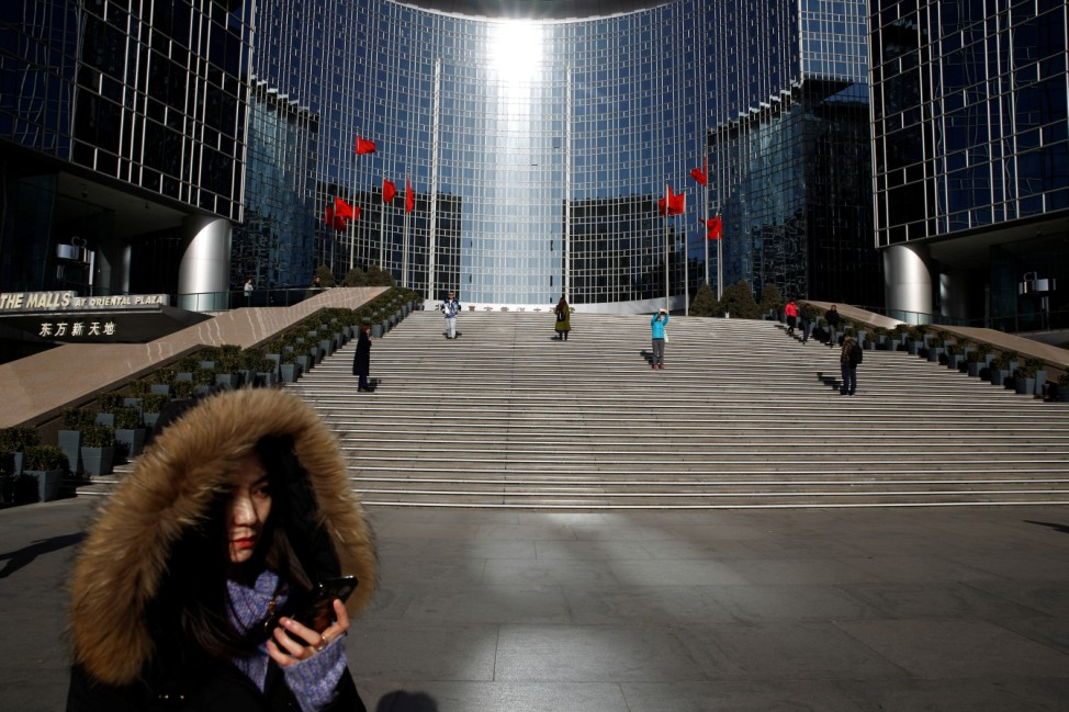A woman uses her phone as she waits for a taxi outside the Grand Hyatt hotel in Beijing