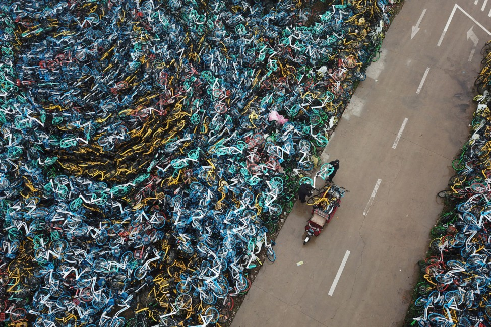 Urban management officers transport a bicycle next to piled-up bicycles of bike-sharing services in Hefei