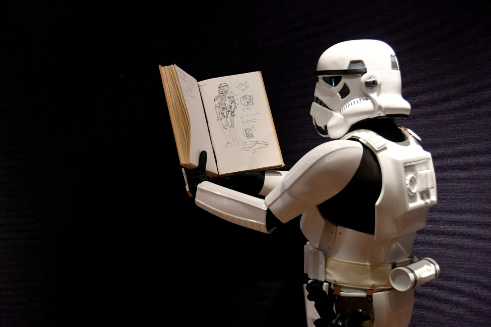 A man wearing a storm trooper costume holds a sketchbook belonging to costume designer John Mollo, and showing illustrations for Star Wars costumes, during a photo-call ahead of an auction at Bonhams in central London