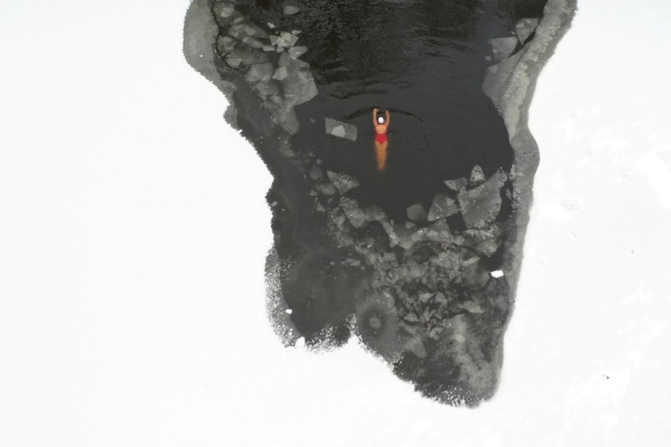 Winter swimmer swims in a frozen river at a park in Shenyang