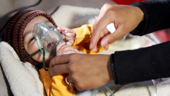 FILE PHOTO: A mother holds a hand of her malnourished child at a malnutrition treatment centre in Sanaa