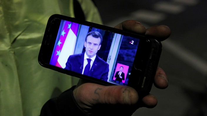 A protester wearing a yellow vest listens to French President Emmanuel Macron who addresses the nation about the 'yellow vests' crisis at a roundabout in Fontaine-Notre-Dame