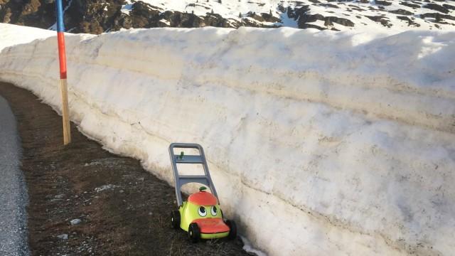 Alpen: Der Spielzeug-Rasenmäher eines Kindes harrt im Dorf Maloja auf den nächsten Sommer.