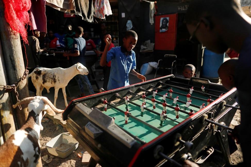 Boys play table soccer near goats in Medina neighbourhood
