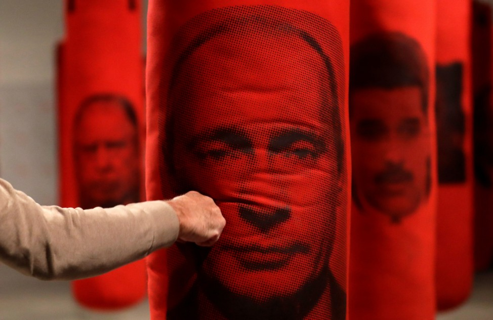A visitor hits a punching bag with an image depicting Russian President Vladimir Putin, in Prague
