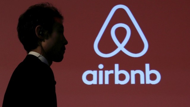 FILE PHOTO: A man walks past a logo of Airbnb after a news conference in Tokyo