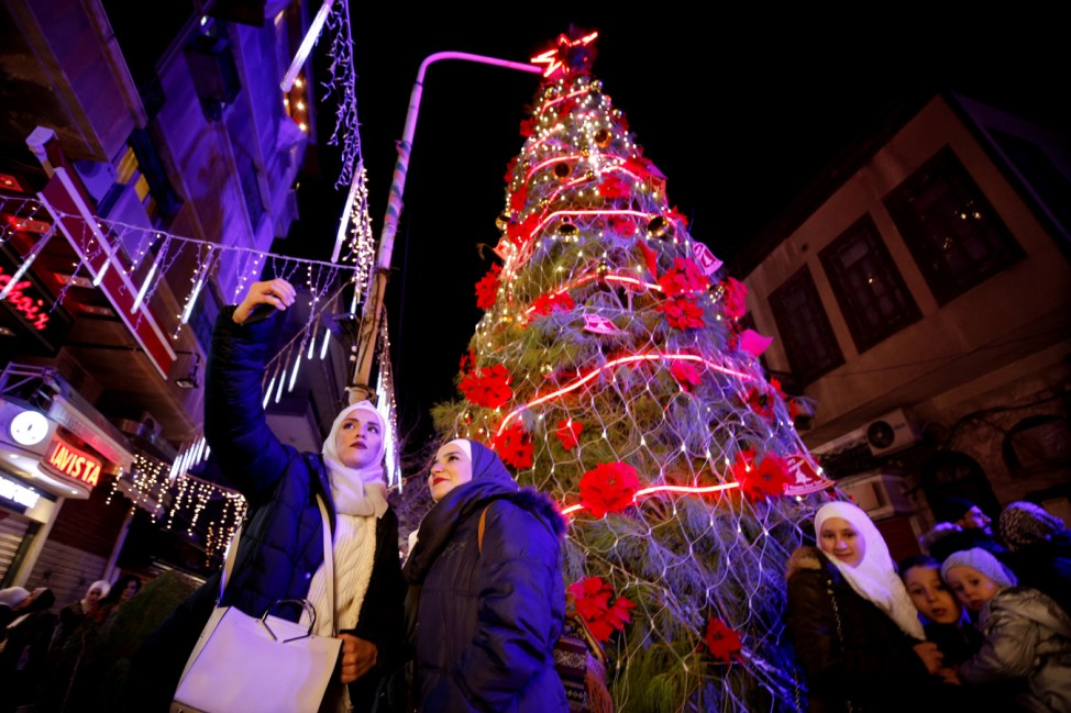 People take a selfie in front of a Christmas tree in the Qasaa district