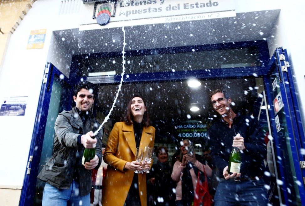 Kiosk owners Juan, Maria and Miguel Angel celebrate outside their kiosk, where the winning number was sold with the biggest prize of Spain's Christmas Lottery 'El Gordo' in Ronda