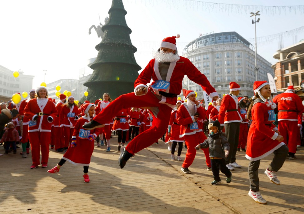 People dance before the annual Santa Claus city race in Skopje