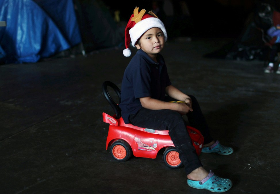 A migrant boy, part of a caravan of thousands from Central America trying to reach the United States, sits on a toy car as he celebrates Christmas at a temporary shelter in Tijuana