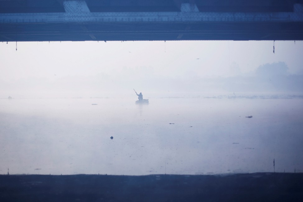 A man paddles a handmade boat across the Yamuna river on a foggy winter morning in New Delhi