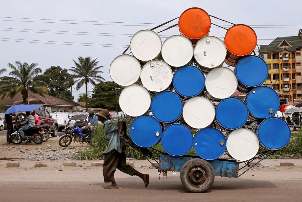 Man pulls a cart with barrels in Kinshasa