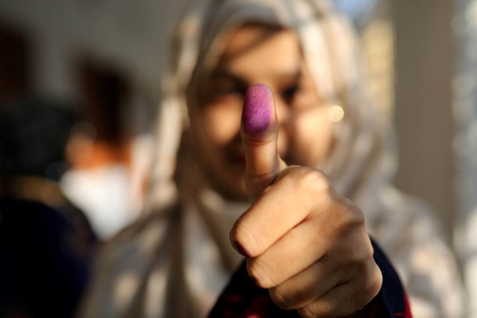 A woman displays her inked thumb after casting her vote for the general election in Dhaka